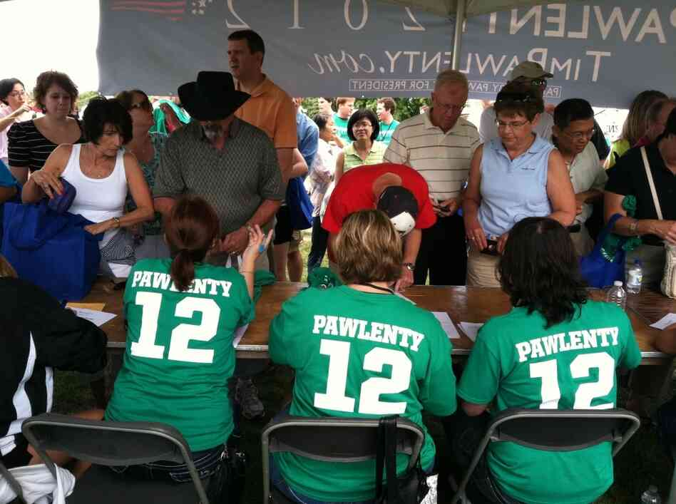 "Volunteers for former Minnesota Gov. Tim Pawlenty take information from participants and hand out  ""Pawlenty 2012"" T-Shirts at a table near a food tent the campaign set up for supporters."
