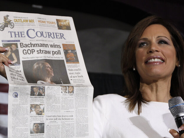 Republican presidential candidate Rep. Michele Bachmann, R-Minn., holds up a newspaper saying that she won the GOP Straw Poll as she speaks at the Black Hawk County Republican Party Lincoln Day Dinner in Waterloo, Iowa, Sunday, Aug. 14, 2011.