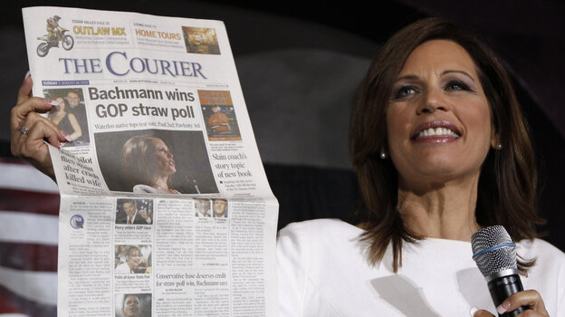 Republican presidential candidate Rep. Michele Bachmann, R-Minn., holds up a newspaper saying that she won the GOP Straw Poll as she speaks at the Black Hawk County Republican Party Lincoln Day Dinner in Waterloo, Iowa, Sunday, Aug. 14, 2011. (AP Photo/Charles Dharapak)