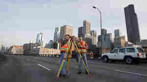 Washington Department of Transportation surveyors Mark McDonald (left) and Richard Torres work atop Alaskan Way Viaduct in downtown Seattle in 2009. The viaduct, which was constructed in the 1950s, is slated to be replaced by a deep-bore tunnel. A 2001 earthquake seriously weakened the structure, and engineers say another  hard shake could bring it down.
