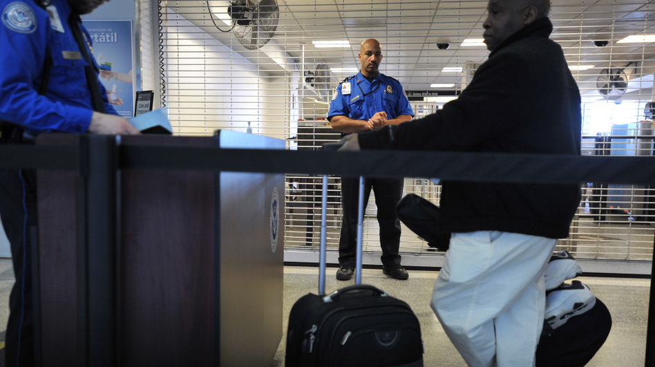 A TSA employee being trained in behavioral pattern recognition watches passengers in line at Boston's Logan International Airport in 2010. This week, Logan will become the first U.S. airport to require every passenger to go through behavioral profiling.