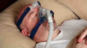 Many people with sleep apnea wear a CPAP machine mask in bed to help them breathe.
