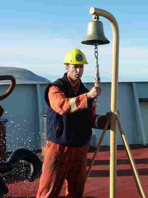 Seaman Bernie Noseworthy, of Newfoundland, provides the traditional signal while the Louis' anchor is raised from the Arctic waters. The bell is rung for each shot of chain — 15 fathoms, or 90 feet — that comes back onboard.