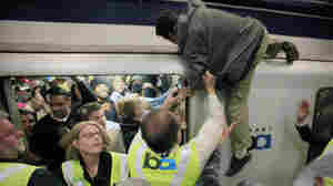 A man is pulled off a commuter train at the Civic Center BART station on July 11 in San Francisco after climbing on top of it during a protest against the July 3 shooting by transit police of Charles Blair Hill. On Thursday, BART officials blocked cell service in some stations to prevent another protest.