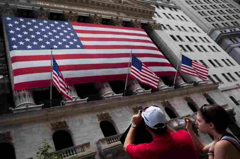 Tourists photograph the New York Stock Exchange building on Wall Street. Of the estimated 60 million 401(k) participants, 87 percent have at least a portion of their portfolio in stocks.