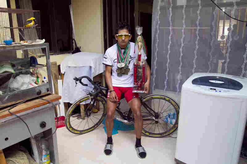 Johan Cardenas, 16, poses with his medals, one of his three bikes and one of his several trophies in his home in Duitama, Colombia. The promising young rider hopes to join the ranks of world-class cyclists from Colombia — who are known for their ability to withstand pain.