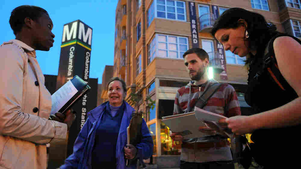 Maureen Evans Arthurs, left, and Stephen Miller join Marty Langelan, second from left, and Brooke Applegate, right, in Columbia Heights for a community safety audit. The volunteer auditors note graffiti, dark streetlights and any incidents of harassment.