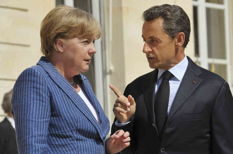 France's President Nicolas Sarkozy, right, speaks to German Chancellor Angela Merkel as he welcomes the German leader at the Elysee Palace in Paris.
