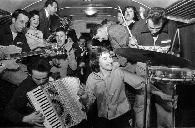 February 1957:  Bill Haley's band The Comets play in the cramped space of a railway carriage en route to London.  (Photo by Harry Kerr/BIPs/Getty Images)