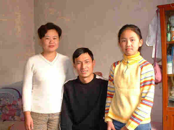 Mandy, age 11, with her  parents in the one-room apartment they shared with her grandmother in Beijing. The room was  about the same size as her freshman double at college last  year.