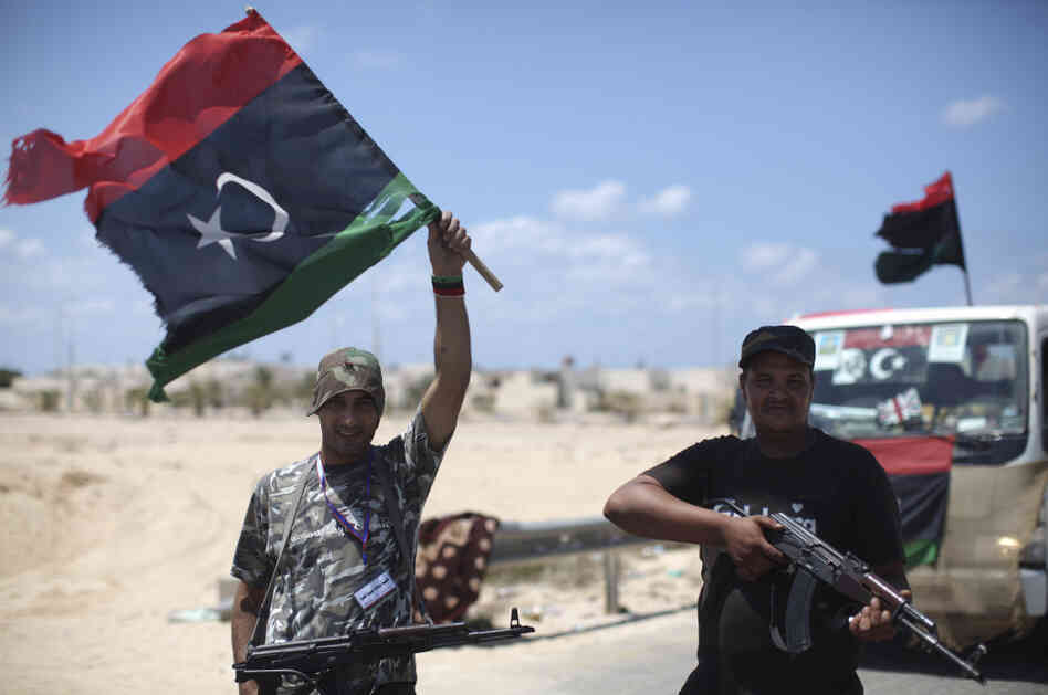 Rebel soldiers pose for photos near the entrance of the town of Brega, Libya.
