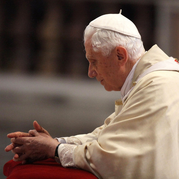 Pope Benedict XVI prays in front of the coffin of his predecessor, John Paul II, at St. Peter's Basilica at the end of a beatification ceremony on May 1, 2011, in Vatican City.