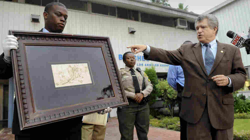 """Los Angeles Sheriff lead detective Clarence Williams, left,  and Los Angeles County sheriff's spokesman Steve Whitmore, right, display the recovered $250,000 quill pen Rembrandt drawing known as """"The Judgment."""""""