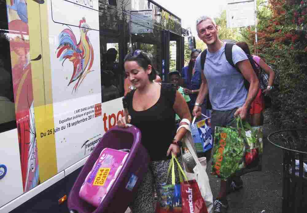 After a day of shopping, residents of Geneva get on a bus to head home this past Saturday, carrying 250 euros' worth of groceries they bought at the Carrefour supermarket in Ferney-Voltaire, France.
