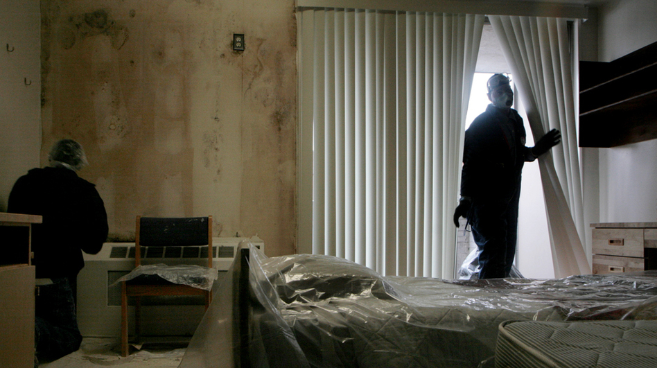 Workers for IAP World Services peel moldy wallpaper off the walls and make repairs in one of two  rooms in Building 18 at  Walter Reed in Washington, D.C., in February 2007.