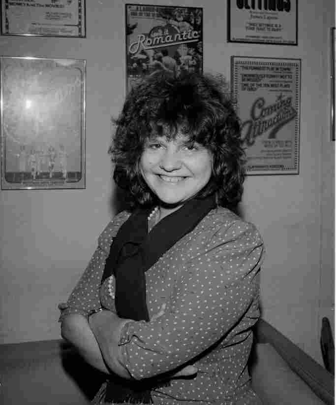 Wendy Wasserstein in 1985, beneath a poster for her play Isn't It Romantic. Wasserstein's plays examined the place where the upheaval witnessed by the baby boom generation met the demands of family and professional life.