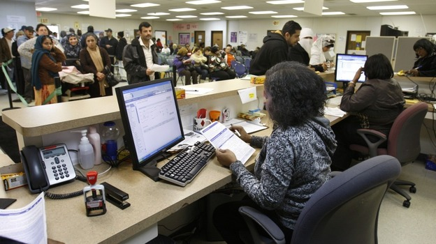 Michigan Department of Human Services caseworker Sandy Satchel works at the Family Independence Agency in Detroit. In the past few years, welfare caseloads have dropped 2 percent in Michigan while unemployment has risen 54 percent, a trend that's reflected in other states. (AP)