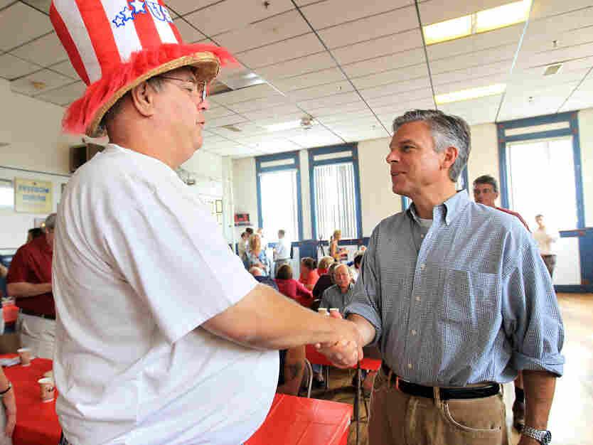 Jon Huntsman, r, shakes a man's hand in Nashua, N.H., Saturday, Aug. 13, 2011.