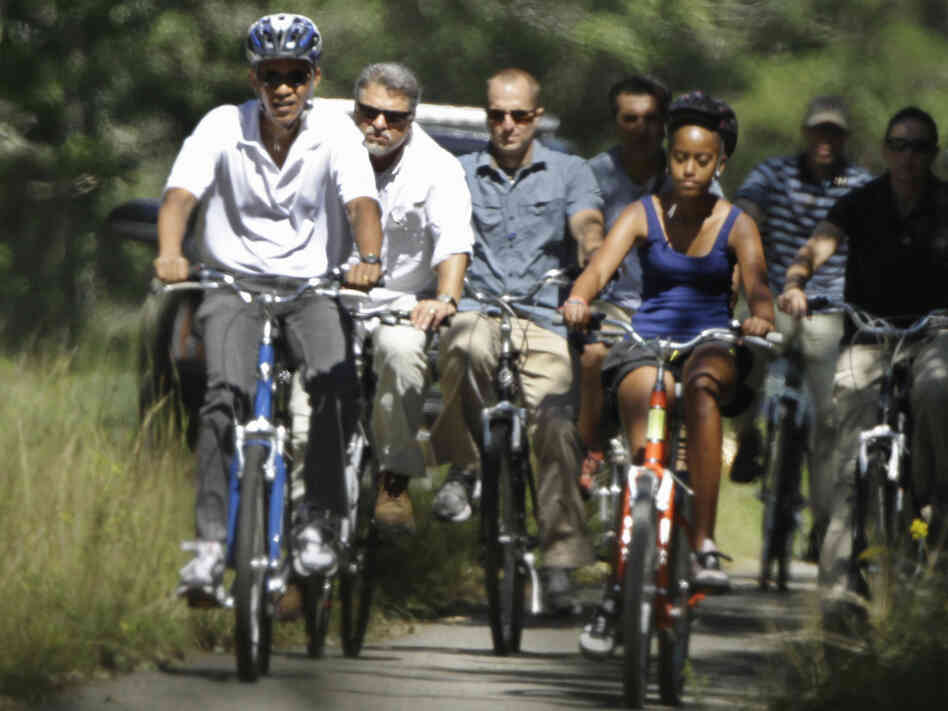 President Obama and his daughter Malia ride bicycles along a path on Martha's Vineyard, Mass., in August 2010. Obama is returning to the island for his vacation this summer.