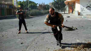 Two Libyan rebel fighters battle with snipers holed up in a hotel at the main square of Zawiya, a city 30 miles west of Tripoli, on Thursday. The rebels entered the key coastal city this week.