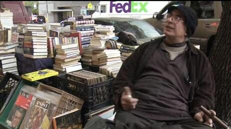 Charles Mysak sells books on a street corner. And his car (behind the stacks) stays parked right there.