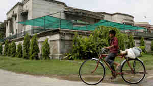 A boy rides a bike past the house of kidnapped American development expert Warren Weinstein in Lahore, Pakistan, on Monday.