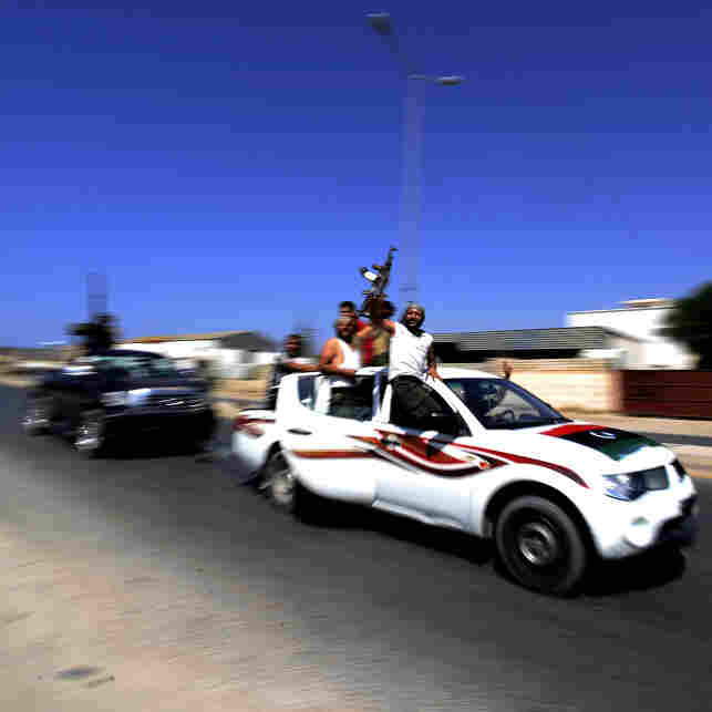 Libyan rebels raise their guns in celebration as they drive through the main road leading to Zawiya. The opposition claimed full control of the strategic city, 30 miles west of Tripoli, on Saturday.