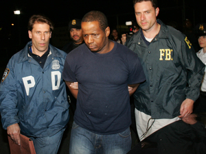 James Cromitie, center, is led by police officers from a federal building in New York, Thursday, May 21, 2009, after being arrested on charges related to a bombing plot in the Bronx. The arrest of Cromitie and three other Muslim ex-convicts in the alleged homegrown terror plot is renewing fears about the spread of Islamic extremism in the nation's prisons. (AP Photo/Robert Mecea)