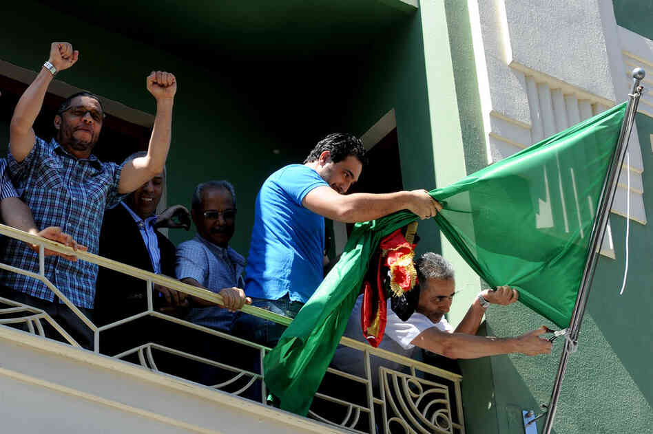 Libyan consul Abdulmacit Ali Said (right) removes the Gadhafi regime flag in Istanbul, Turkey, on Monday.