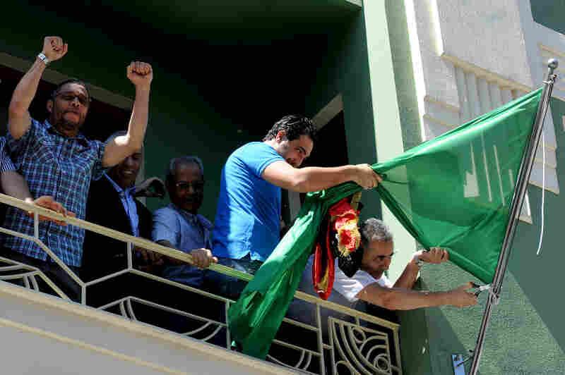 Libyan consul Abdulmacit Ali Said (right) removes the Gadhafi regime flag in Istanbul, Turkey, on Monday.