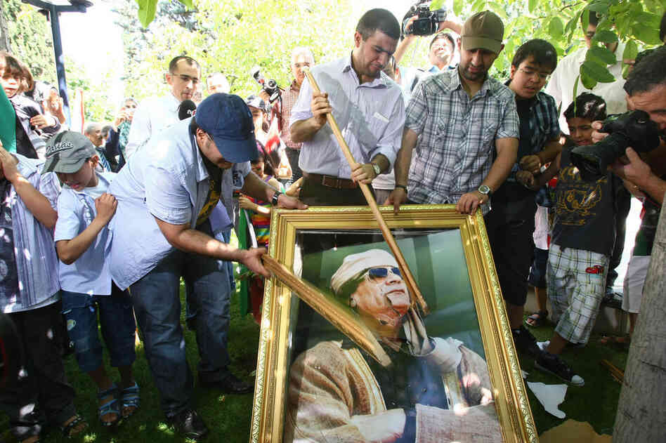 Demonstrators smash a portrait of Moammar Gadhafi during a protest in Ankara on Monday.
