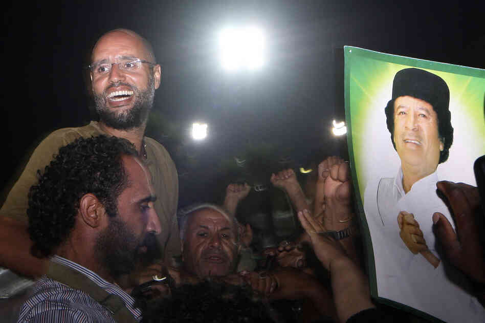 Seif al-Islam Gadhafi (top left) is surrounded by supporters and journalists at his father's residential complex in Tripoli early Tuesday. Fresh fighting erupted in Tripoli hours after his return.
