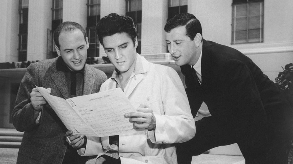 "Jerry Leiber (right) looks over Elvis Presley's shoulder at the sheet music for ""Jailhouse Rock"" in Los Angeles in 1957. His songwriting partner Mike Stoller stands to the left."