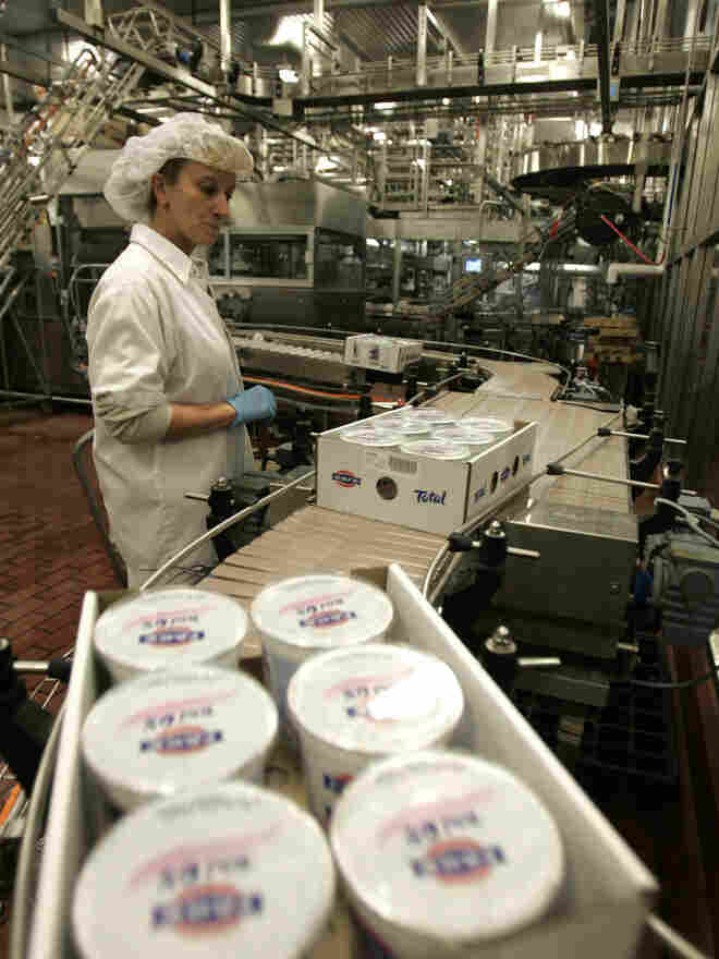 A worker monitors the production line as cases of Fage yogurt are produced in Johnstown, N.Y., in 2008. Fage and Chobani lead the pack of best-selling Greek-style yogurt brands.
