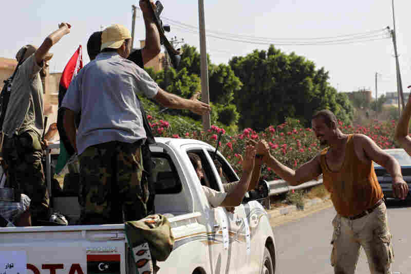 Local residents greet advancing rebel fighters outside Tripoli on Monday.