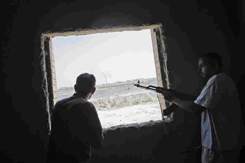Rebel fighters watch the fighting near Gadhafi's compound Tuesday.