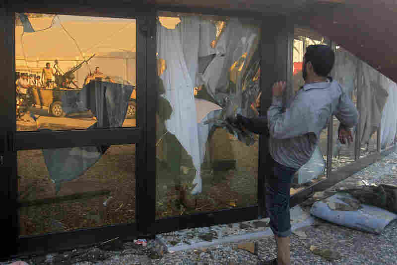 A Libyan rebel breaks the glass of Moammar Gadhafi's main compound in Tripoli on Tuesday.