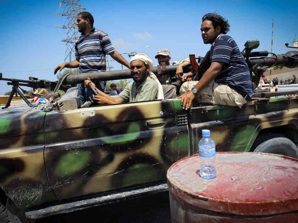 Libyan rebel fighters sped towards the front line of fighting in the village of Al-Mayah, just west of Tripoli, on Sunday.