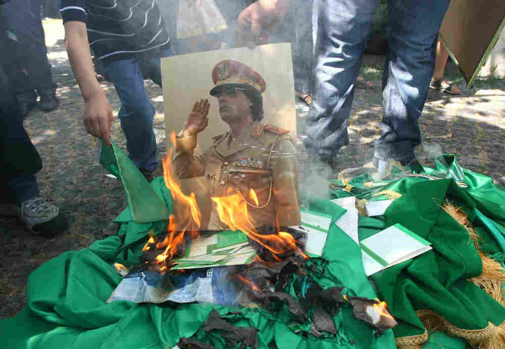 Protesters burn a portrait of Libyan leader Moammar Gadhafi and copies of his Green Book outside the Libyan Embassy in Ankara