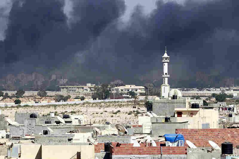 Smoke rises above downtown Tripoli near fighting at Gadhafi's compound.