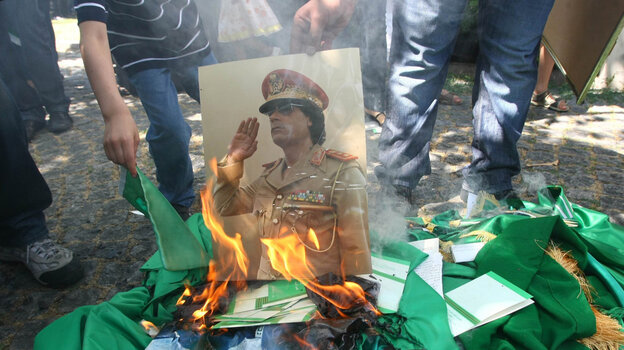 Protesters burn a portrait of Libyan leader Moammar Gadhafi and copies of his Green Book outside the Libyan Embassy in Ankara. Turkey, on Monday. Libyan rebels have taken many parts of the Libyan capital, Tripoli, as they try to oust Gadhafi.