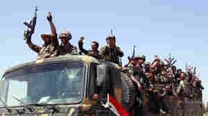 Syrian soldiers shout slogans in support of President Bashar Assad Aug. 10 as they withdraw from the city of Hama after a 10-day military operation to quell pro-democracy protests. This photo was taken during a government-guided tour.