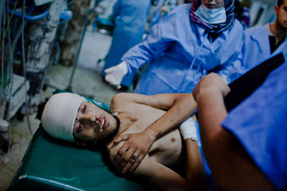 A Libyan rebel fighter receives medical attention after being brought in with a gunshot wound to his head at the Tripoli Central Hospital.