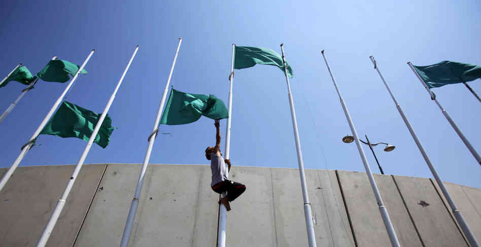 Libyan rebels remove the green flags from poles at the Abu Salim square in Tripoli on Aug. 26 after the opposition forces announced the transfer of their leadership to the capital.