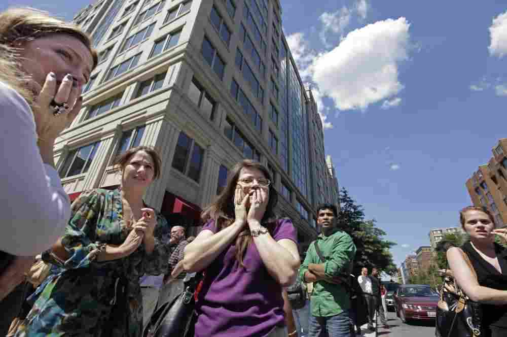 Office workers gather on the sidewalk in downtown Washington, Tuesday, moments after a 5.8 magnitude tremor shook the nation's capit