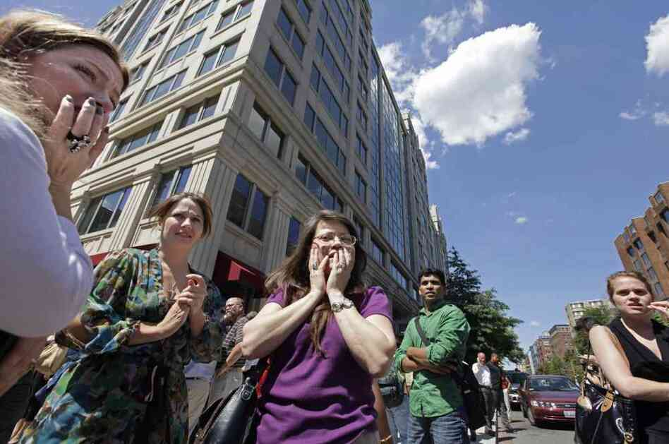 Office workers gather on the sidewalk in downtown Washington, Tuesday, moments after a 5.8 magnitude tremor shook the nation's capital.
