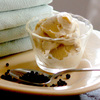 A bowl of Black Pepper Ice Cream on a platter with a spoonful of peppercorns and folded linens