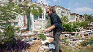 On August 19, Jim James of My Morning Jacket pulls a silk rose from the rubble of a house in Tuscaloosa that was destroyed by a tornado in April.