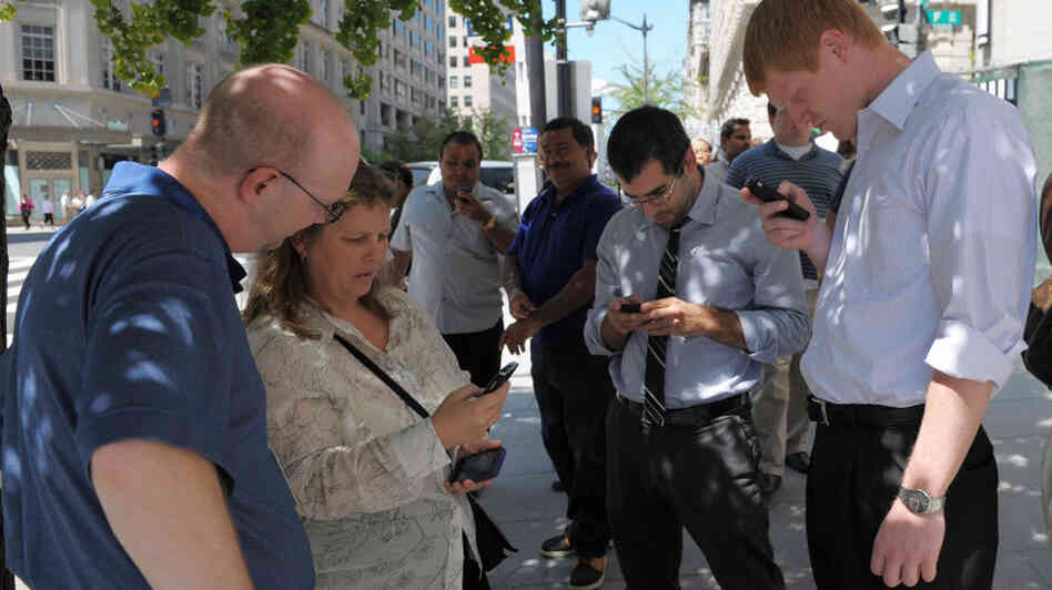 People check their smartphones while standing in the street shortly after an earthquake struck Washington on Tuesday.