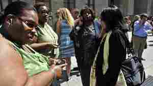 People reach for their cellphones outside the courthouse in Manhattan after an earthquake rattled the East Coast on Tuesday.